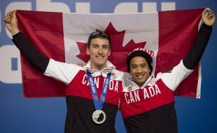 Les patineurs de vitesse canadiens Denny Morrison et Gilmore Junio tiennent un drapeau du Canada aux Jeux olympiques d'hiver de Sotchi, le 6 février 2014. (Mention de source : LA PRESSE CANADIENNE/Adrian Wyld)