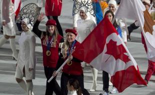 Les bobeuses Kaillie Humphries (à droite) et Heather Moyse entrent dans le stade en portant le drapeau canadien aux cérémonies de clôture des JO d'hiver de Sotchi. (LA PRESSE CANADIENNE/Adrian Wyld)