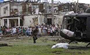 Le vendredi 22 nov. 2013, des survivants du récent typhon regardent le personnel de l'Armée de l'air philippine décharger d'un hélicoptère des sacs d'approvisionnement de secours dans la ville de Tanauan, province de Leyte, région centrale des Philippines. (AP Photo/Bullit Marquez)
