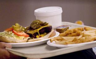 Dans un restaurant-minute de Toronto, un consommateur tient le plateau sur lequel se trouve son repas de midi. (THE CANADIAN PRESS/Chris Young)