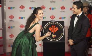 Les patineurs artistiques Tessa Virtue et Scott Moir signent leur étoile alors qu'ils sont intronisés dans l'Allée des célébrités canadiennes 2018 pendant un événement médiatique avec tapis rouge à Toronto le 1er décembre 2018. (THE CANADIAN PRESS/Chris Young)