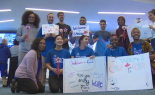 Un  groupe d'étudiants, incluant Tamasha Hussein (en bas à droite), accueille à Vancouver Clemance Bisamu et d'autres nouveaux étudiants réfugiés. (Jon Hernandez via cbc.ca)
